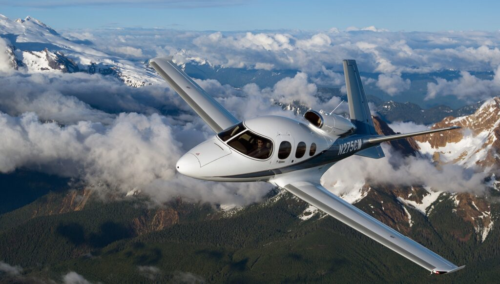 Cirrus Vision Jet G2+ flying above some clouds and mountains